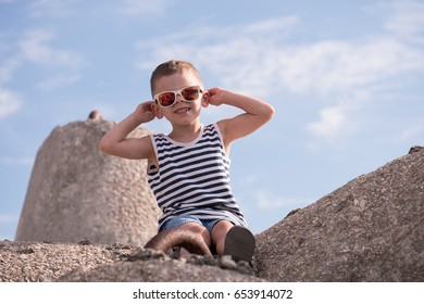 Cute smiling little boy in sunglasses and sailor stripes shirt sitting on a concrete breakwater on blue sky with clouds background