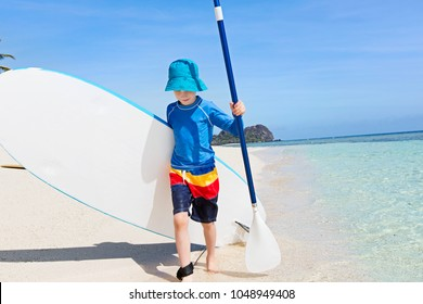 cute smiling little boy walking with surfboard and paddle at the beach enjoying active vacation at the tropical island at fiji, south pacific