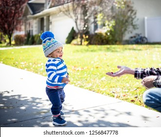 Cute smiling little boy walking towards an outstretched hand with a free handout of food or a treat. trying to get a delicious treat. Concept photo for giving