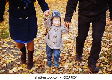 Cute smiling little boy walking with parents holding hands in autumn nature