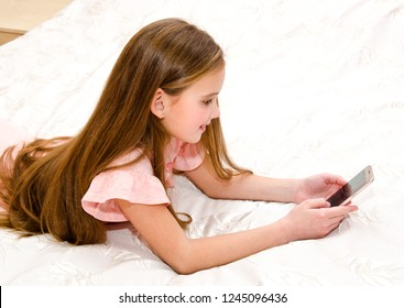 Cute smiling little girl child with her mobile phone smartphone lying on the bed technology and internet concept