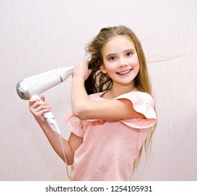 Cute smiling little girl child drying her long hair with hair dryer isolated
