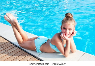 Cute smiling little girl child lying near swimming pool and having fun on summer vacation