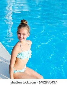 Cute smiling little girl child sitting near swimming pool and having fun on summer vacation