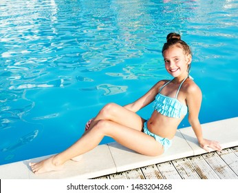 Cute smiling little girl child sitting hear the swimming pool on summer vacation