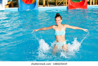 Cute smiling little girl child having fun in the swimming pool on summer vacation