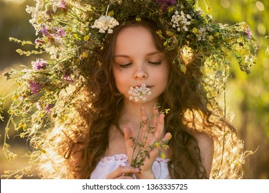 Cute smiling little girl with flower wreath on the meadow at the farm. Portrait of adorable small kid outdoors. Midsummer.