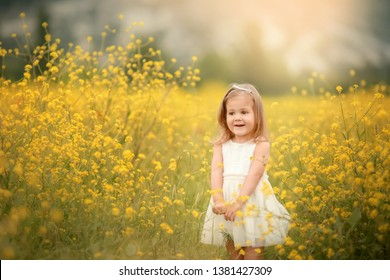 Cute smiling little girl with flower wreath on the meadow at the farm. Portrait of adorable small kid outdoors. Midsummer. Earth Day.