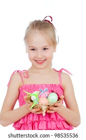 cute smiling little girl holding Easter eggs in basket