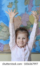 Cute smiling little girl holds hand up against map background