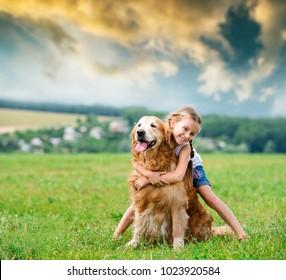 Cute smiling Little girl hugging retriever in the summer park