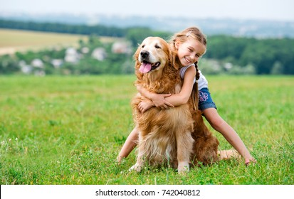 Cute smiling Little girl hugging retriever in the summer park