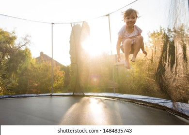 Cute smiling little girl jumping high on trampoline