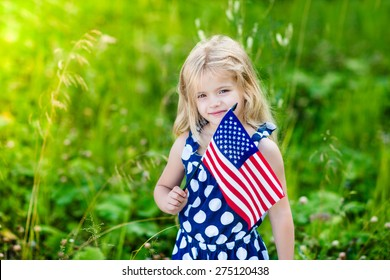 Cute smiling little girl with long curly blond hair holding an american flag on sunny day in summer park. Independence Day, Flag Day concept
