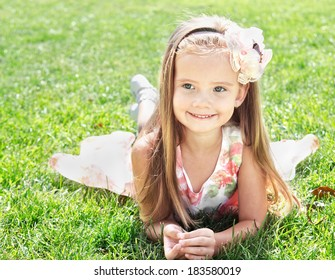 Cute smiling little girl lying on grass outdoor