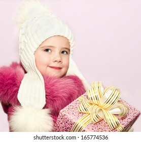 Cute smiling little little girl with present in christmas time