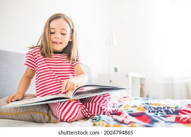 Cute smiling little girl reading a book at home. Children literature concept. Little girl learning to read. Preschooler education themed background.