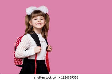 Cute smiling little girl in school uniform and white bows with backpack on pink background. Back to school. Education and school concept