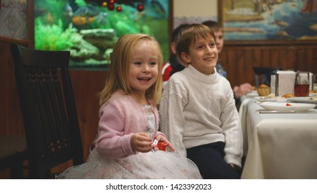 Cute smiling little girl sitting at the table with her friend on the birhday party