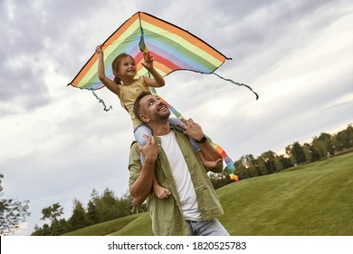 Cute smiling little girl sitting on shoulders of her dad and playing with colorful kite, small daughter and father spending time together in park on a warm day