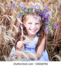 cute smiling little girl with a wreath on his head in a field of wheat close-up