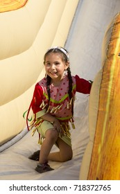 Cute smiling little native girl in indian dress in inflatable slide, Pow Wow, Wendake, Quebec, June 25, 2016