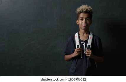 Cute smiling mixed-race schoolboy with dyed blond hairs wears backpack standing indoors pose against black wall looking at camera. Back to school, pretty 10s boy portrait on chalkboard  background