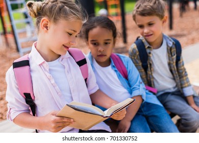 cute smiling multiethnic schoolkids with backpacks reading book together