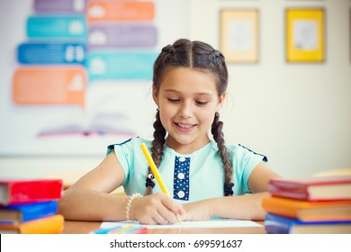 Cute smiling schoolgirl at school during lesson