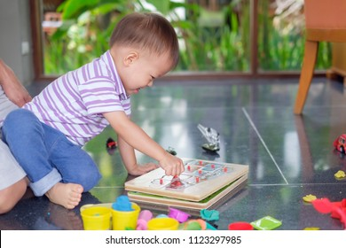 Cute smiling smart little Asian 2 years old toddler boy child sitting on parent lap playing with puzzle shapes in living room / play room at home, Problem solving, Fine motor skill development concept
