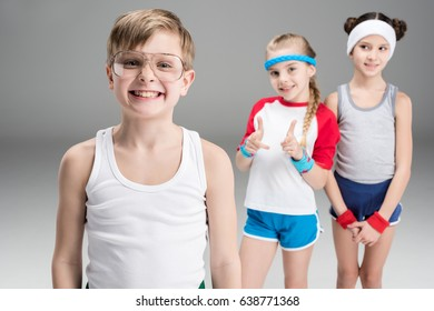 Cute smiling sporty girls looking at happy boy in sportswear, children sport concept