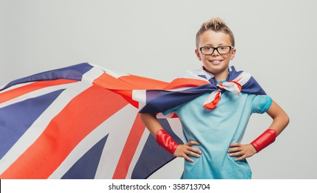 Cute smiling superhero boy posing with arms akimbo and wearing a British flag as a cape, learning languages concept