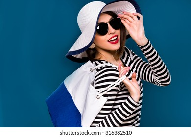 Cute smiling woman, with dark hair, wearing in striped blouse, black sunglasses and white hat, is posing with white and blue bag, on blue background, in studio, waist up
