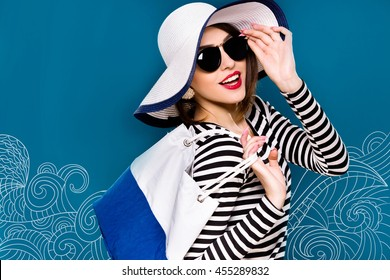 Cute smiling woman, with dark hair, wearing in striped blouse, black sunglasses and white hat, is posing with white and blue bag, on blue background with sea pattern, waist up