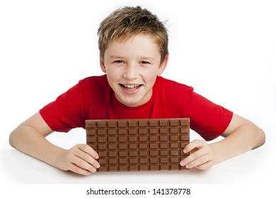 Cute smiling young boy eating a very big bar of chocolate. Wearing a red T-shirt, shot in the studio on a white background.