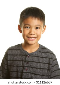 Cute smiling,happy Filipino boy on a white background. He is missing one front tooth.