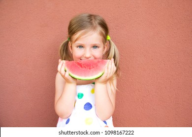 Cute, smilling little girl eating watermelon. Red background. Summer concept.