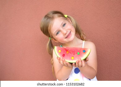 Cute, smilling little girl eating watermelon. Red background with rainbow. Summer concept.