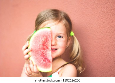 Cute, smilling little girl and watermelon. Red background. Summer concept.