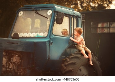 Cute smudgy little boy without t-shirt and shoes, and in pants with suspenders sitting on the tractor and looking inside dreaming to be a tractor-driver. Image with selective focus and toning