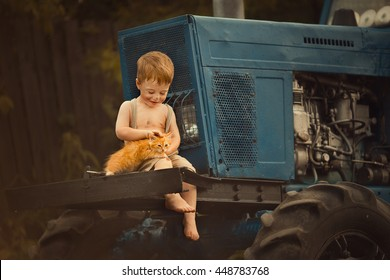 Cute smudgy little boy without t-shirt and shoes, and in pants with suspenders sitting on the tractor  in the countryside and stroking a ginger kitten. Image with selective focus and toning