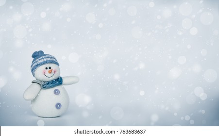 Cute snowman hand showing copy space with cold grey and snow fall background