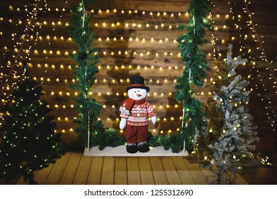 cute snowman standing in christmas wooden house