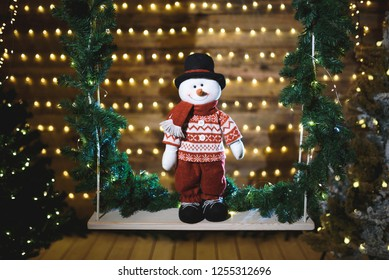 cute snowman standing on christmas seesaw