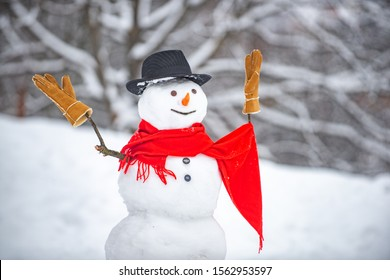 Cute snowmen standing in winter Christmas landscape. The snowman is wearing a fur hat and scarf. Snowman with light star in Christmas day