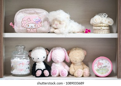 Cute soft plushes. Lovely dolls are sitting on the little girl's headboard and other cute accessories. Selective focus on kawaii sheep plush doll on top shelf.