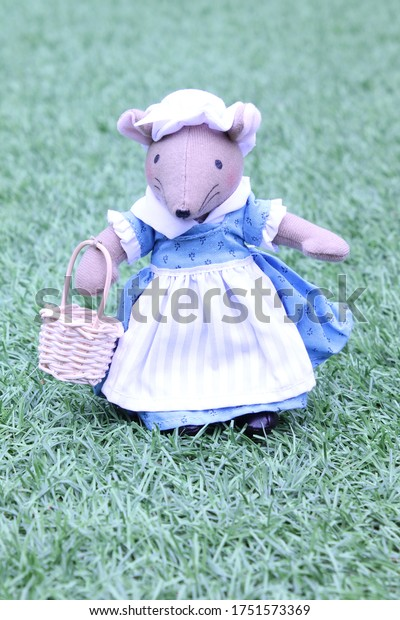 Cute soft toy mouse wearing a vintage blue dress, white apron and a white cap, holding a wicker basket on a grass background