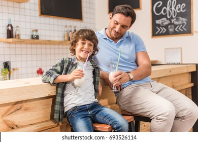 cute son and his father drinking milkshakes in cafe