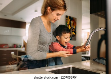 Cute son washing hands with support from his mother in the kitchen sink. Woman helping little boy to wash hands after cooking.