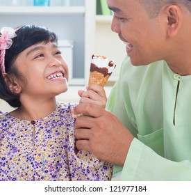 Cute Southeast Asian girl feeding ice cream to father. Malay Muslim family lifestyle
